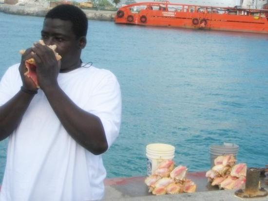 Man blowing a conch shell in Nassau, Bahamas. Photo by Tui Cameron