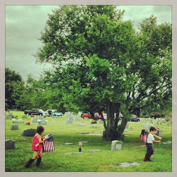 Children placing flags on the veteran's graves in Weatherford, Texas